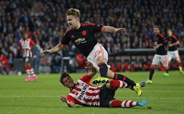 Stoper PSV Eindhovenu Héctor Moreno (dole) fauluje Luka Shawa z Manchesteru United, který musel později vystřídat.