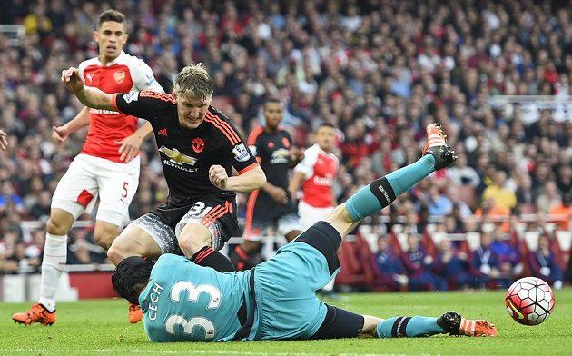 Brankář Arsenalu Petr Čech zasahuje proti Bastianu Schweinsteigerovi.