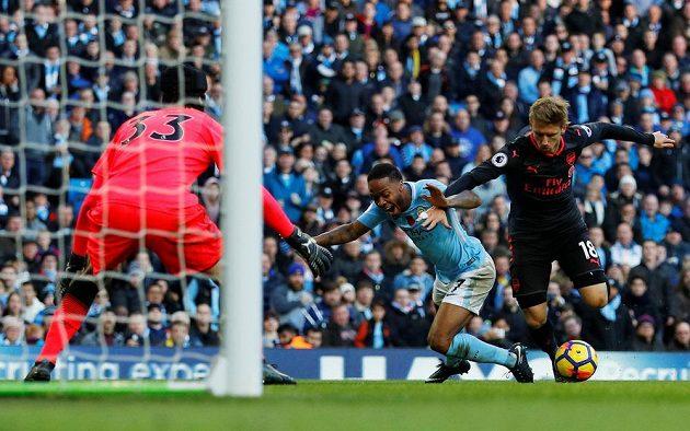 Hráč Manchesteru City Raheem Sterling padá v pokutovém území po zákroku Nacho Monreala a sudí nařídil penaltu. Vše mohl sledovat gólman Kanonýrů Petr Čech.