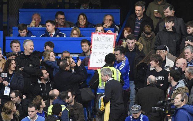 Pořadatel hovoří k majiteli transparentu, na kterém je napsáno: Mourinho byl zrazen hráči a vedením.