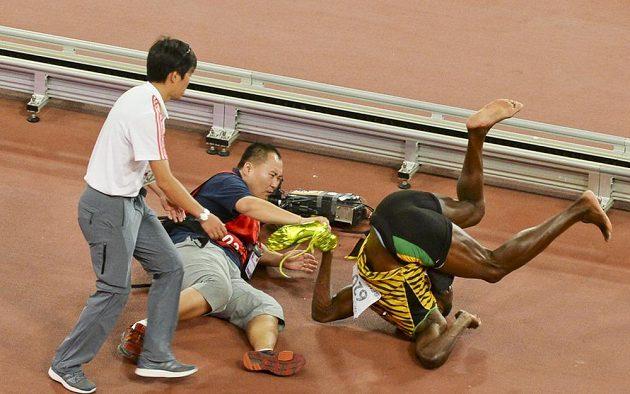 Usain Bolt padá po karambolu s čínským kameramanem.