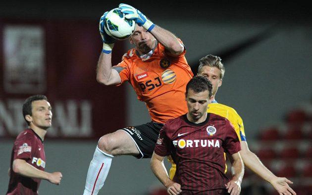 Jihlavský brankář Jaromír Blažek chytá míč před sparťanem Josefem Hušbauerem.