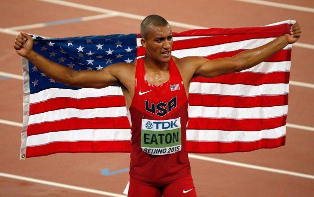 Američan Ashton Eaton slaví s vlajkou po triumfu v desetiboji na MS v Pekingu.