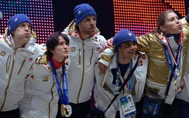 Rychlobruslařka Martina Sáblíková (druhá zleva) a Eva Samková (vpravo) zdraví fanoušky v Olympijském parku na Letné po návratu ze Soči dne 23. února 2014.
