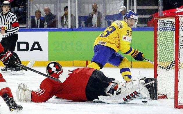 Švýcarský gólman Leonardo Genoni a Viktor Arvidsson ze Švédska. Tady gól nepadl.