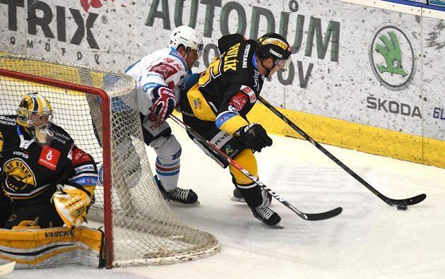 Chomutovský David Kämpf (v bílém) napadá za brankou Litvínova, puk se snaží vyvézt do bezpečí Filip Pavlík.