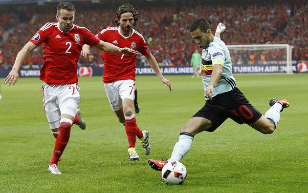 Velšané Chris Gunter a Joe Allen se snaží blokovat střílejícího belgického tvůrce hry Edena Hazarda.