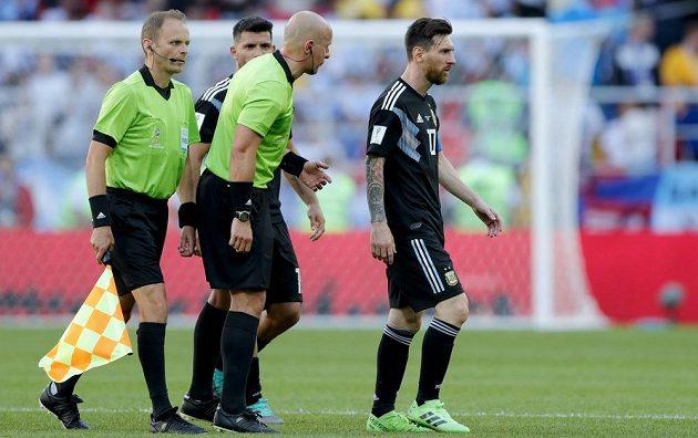 Argentinský fotbalista Lionel Messi kráčí zklamaně ze hřiště. Hvězda nedala penaltu a Argentina jen remizovala s Islandem. Odchod sledují rozhodčí duelu.