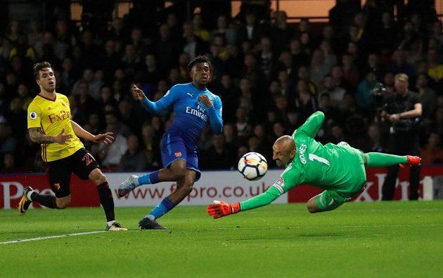Gólman Watfordu Heurelho Gomes zasahuje před Alexem Iwobim (uprostřed) z Arsenalu.