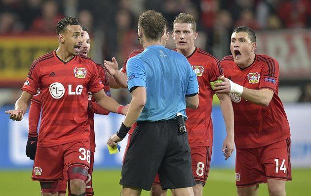 Leverkusenský Kyriakos Papadopulos (vpravo) dostává žlutou kartu od rozhodčího Pavla Královce v úvodním osmifinále Ligy mistrů.