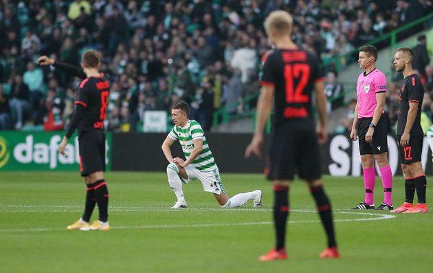 Fotbalista Celtiku Glasgow David Turnbull klečí před zahájením utkání.