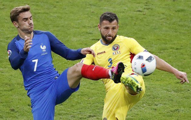 Razvan Rat z Rumunska (vpravo) bojuje o míč s Antoinem Griezmannem z Francie.