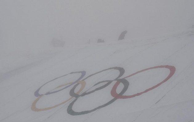 Organizátoři upravují trať pro snowboardkros, která je ponořená do mlhy.