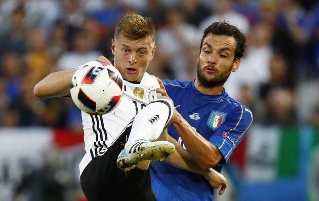 Ital Marco Parolo (vpravo) bojuje o míč s Tonim Kroosem.