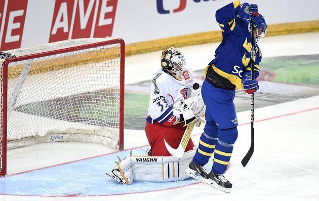 Český brankář Pavel Francouz se snaží dostat puk pod kontrolu před atakujícím švédským útočníkem Jimmiem Ericssonem.