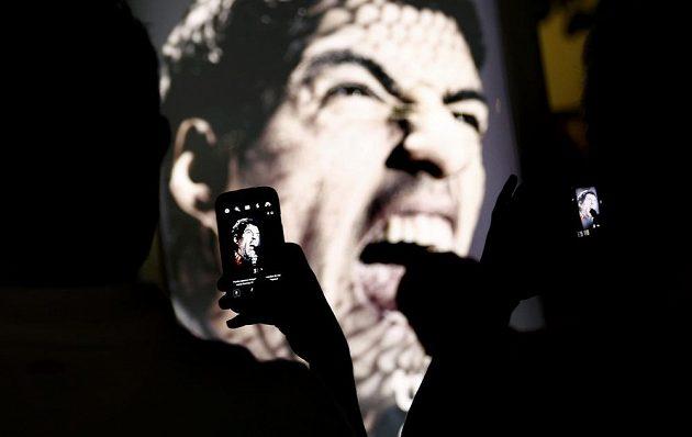 Fanoušci si na plaží Copacabana v Riu fotografují reklamní billboard, na němž Luis Suárez cení zuby.