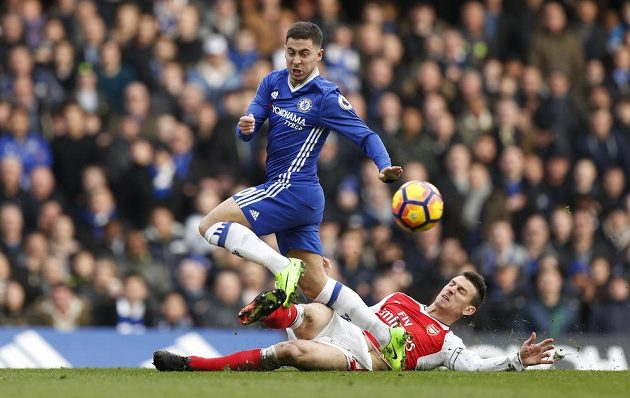 Hvězdu Chelsea Edena Hazarda se skluzem snaží zastavit Laurent Koscielny z Arsenalu.