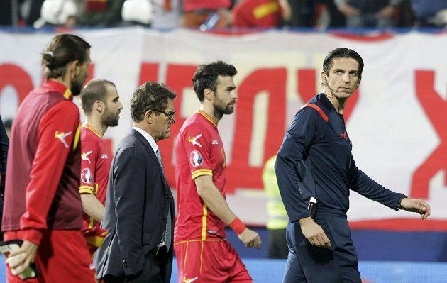 Rozhodčí Deniz Aytekin (vpravo) z Německa odvádí fotbalisty Ruska i Černé Hory ze hřiště po zranění brankáře Igora Akinfejeva. Uprostřed kouč Rusů Fabio Capello