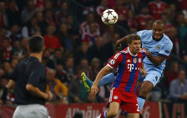 Vincent Kompany (vpravo) z Manchesteru City v souboji s útočníkem Bayernu Thomasem Müllerem.