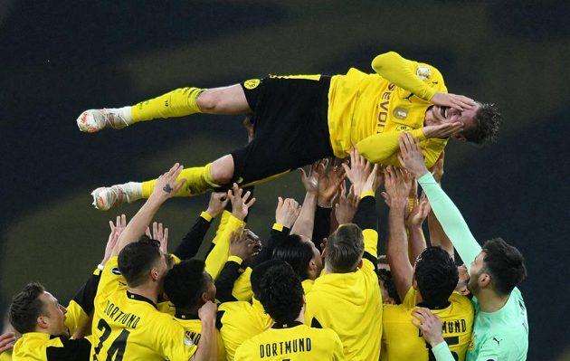 Lukasz Piszczek nad hlavami spoluhráčů po dortmundském triumfu v Německém poháru.