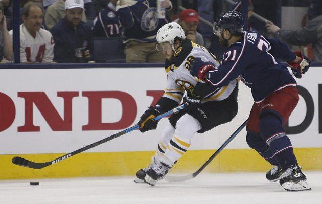 Český hokejový útočník Bostonu David Pastrňák se snaží odolat ataku Nicka Foligna z Columbusu v utkání play off NHL.