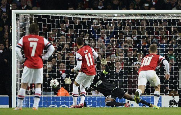 Brankář Olympique Marseille Steve Mandanda chytá střelu z pokutového kopu Mesuta Özila z Arsenalu.