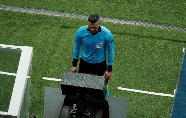 Damir Skomina zkoumá u videa situaci, po níž v závěru nařídil penaltu pro Manchester United.