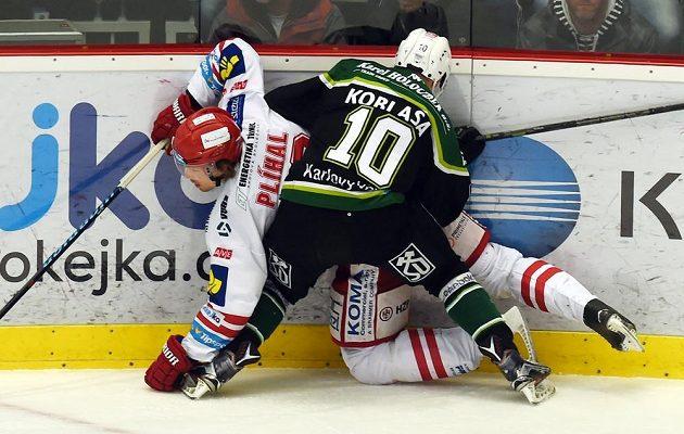Karlovarský útočník Petr Koblasa v souboji s Tomášem Plíhalem z Třince v utkání 41. kola hokejové Tipsport extraligy.