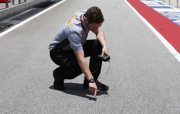 Technik Pirelli měří teplotu asfaltu na okruhu v Sepangu. Tropické vedro v Malajsii umí jezdce pořádně potrápit.
