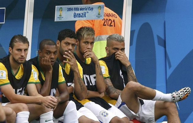Zamyšlená lavička Brazílie po šokujícím úvodu zápasu s Nizozemskem. Zprava Dani Alvés, Neymar, Hulk a další spoluhráči.