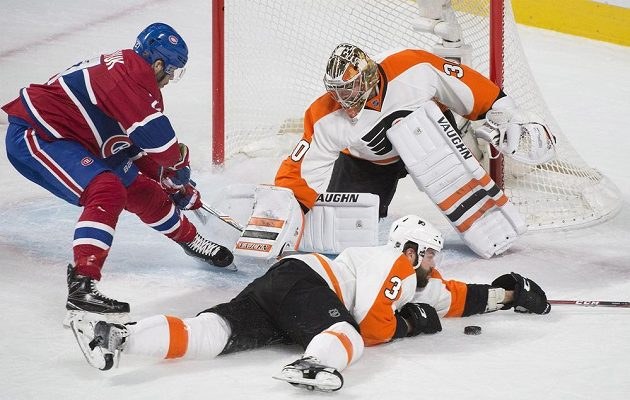 Obránce Philadelphie Radko Gudas (3) blokuje přihrávku v zápase NHL proti Montrealu. Z brány vše pozoruje Michal Neuvirth (30).