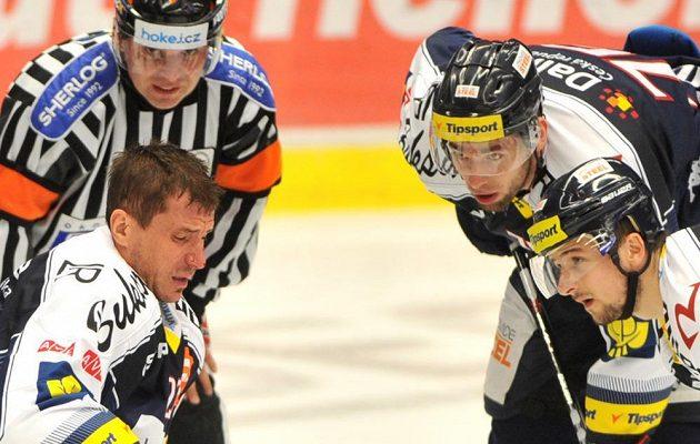 Hokejisté Vítkovic (zprava) Ondrej Šedivý a Richard Stehlík u zraněného spoluhráče Petera Húževky (vlevo).