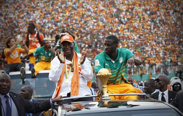 Přivítání novopečených šampiónů v metropoli Abidžanu. Prezident země Alassane Ouattara (vlevo) sedí s trofejí vedle kapitána týmu Yayi Tourého.