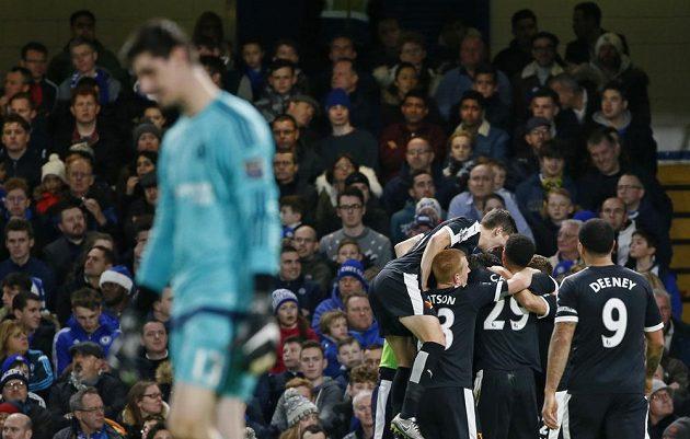 Hráči Watfordu slaví branku Odiona Ighala, v popředí zklamaný gólman Chelsea Thibaut Courtois.