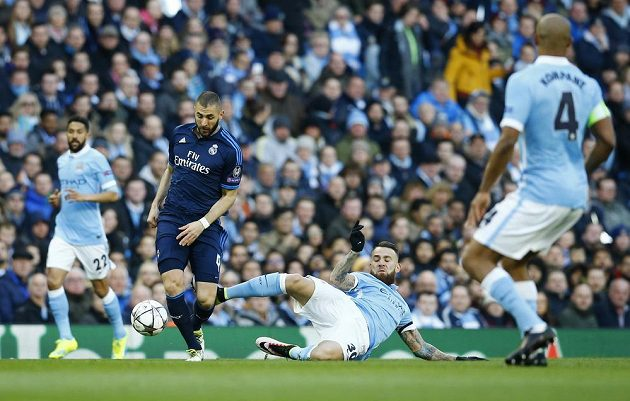 Útočník Realu Karim Benzema (druhý zleva) v souboji s obranou Manchesteru City.