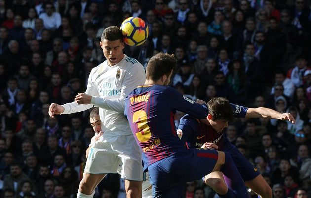 Cristiano Ronaldo z Realu v hlavičkovém souboji s Gerardem Piquém z Barcelony.