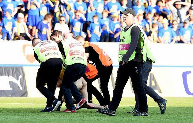 Pořadatelé odvádějí polonahého fanouška, který vběhl na hrací plochu.
