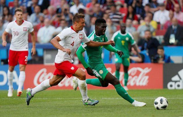 Senegalec Ismaila Sarr v souboji s Polákem Thiagem Cionekem během utkání MS.