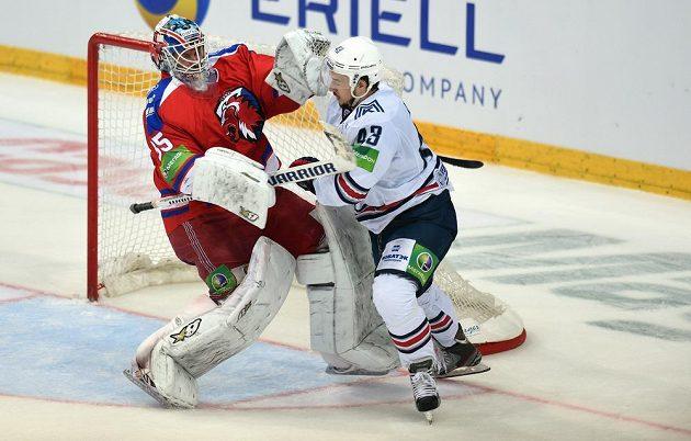 Český útočník Magnitogorsku Jan Kovář (vpravo) fauluje brankáře Lva Praha Petriho Vehanena během utkání finále play off KHL.