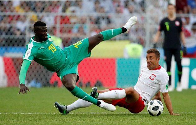 Senegalský fotbalista M'Baye Niang v akrobatické pozici v souboji s Polákem Thiagem Cionekem.