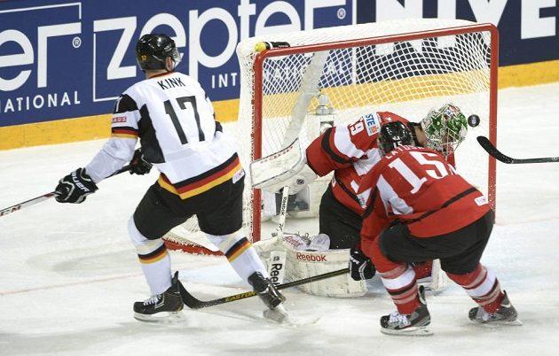 Německý hokejista Marcus Kink (vlevo) dává gól rakouskému brankáři Bernhardu Starkbaumovi.