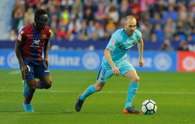 Barcelonský Andres Iniesta v akci během utkání s Levante. Jeho hráč Emmanuel Boateng pohledem kontroluje barcelonskou legendu.