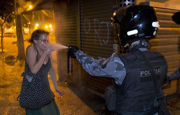 Policista stříká pepřový sprej do očí jedné z demonstrantek v Rio de Janeiro.