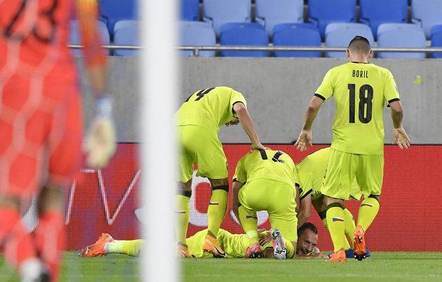 Vladimír Coufal (na zemi) oslavuje se spoluhráči gól proti Slovensku.