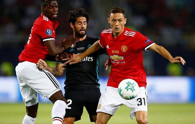Isco z Realu Madrid v obležení hráčů Manchesteru Nemanji Matiče (vpravo) a Paula Pogby.