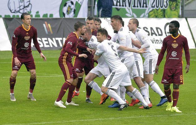 Fotbalisté Karviné (v bílých dresech) a Dukly bojují o výhodnou pozici před brankou pražského týmu v utkání nejvyšší soutěže.