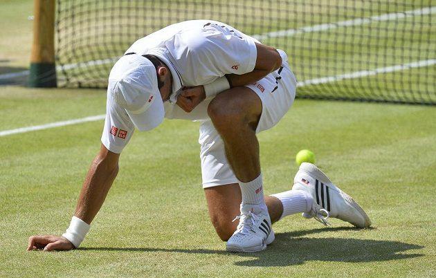 Novak Djokovic se zvedá po pádu.