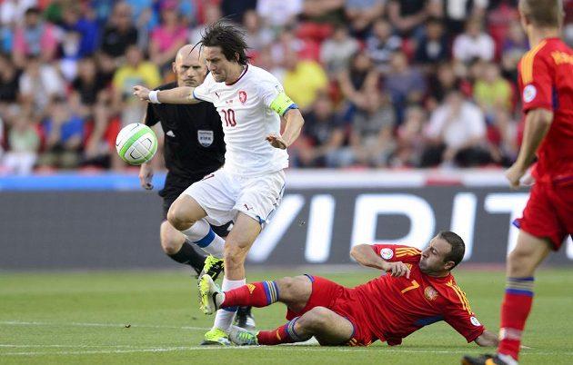Arménský záložník Artur Edigarjan (na zemi s číslem 7) se snaží vypíchnout míč Tomáši Rosickému.