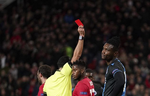 Sudí Serdar Gozubuyuk ukazuje červenou kartu Simonu Delimu z Brugg v odvetě s Manchesterem United.