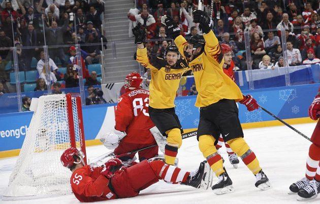 Zaváhání ruského brankáře Košečkina pomohlo Německu k vyrovnání stavu v olympijském finále. Z gólu Felixe Schütze se radují Patrick Hager a Brooks Macek.